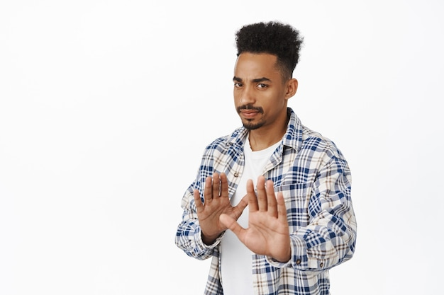 No thank you, he pass. reluctant serious african american guy stretch out hands in stop gesture, rejecting offer, refuse and decline, ask to stay away, dont come closer on white.