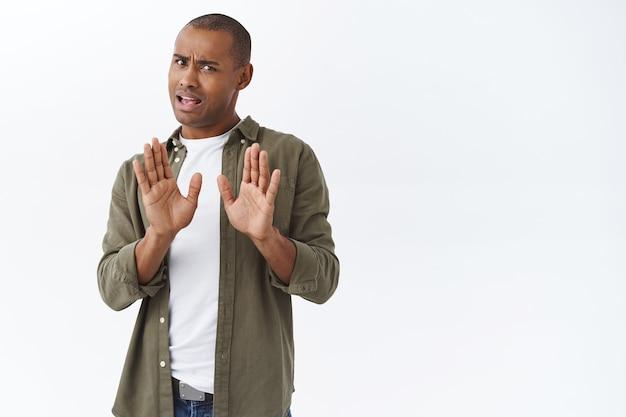 No grazie, passo. ritratto di giovane uomo afroamericano che rifiuta l'offerta delle persone, alzando la mano in blocco