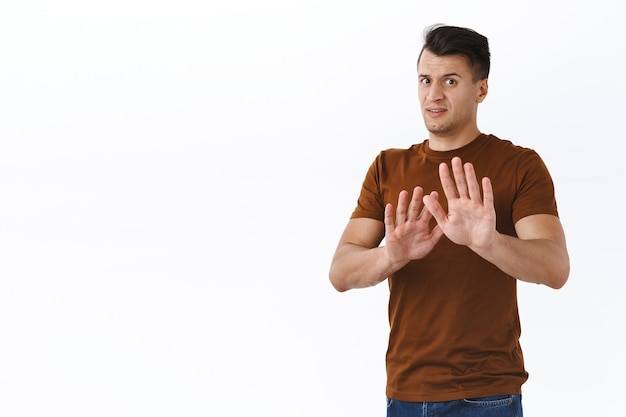 No thank you, please stay away. portrait of anxious and worried handsome young man, raise hands in defense or rejection, shaking to say no or stop