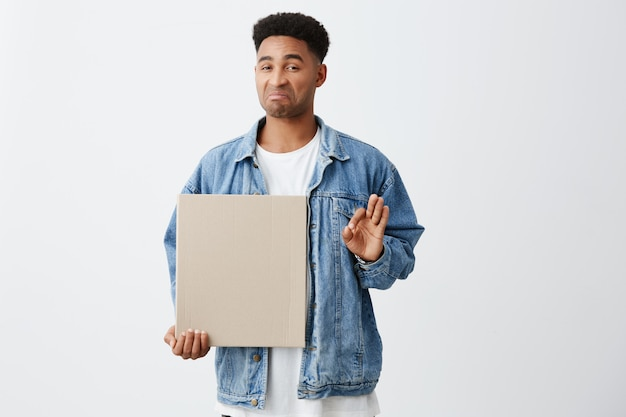 No, thanks. close up of young funny dark-skinned american an with afro hairstyle in white t-shirt and stylish denim jacket holding clean cardboard with disgust and unsatisfied face expression
