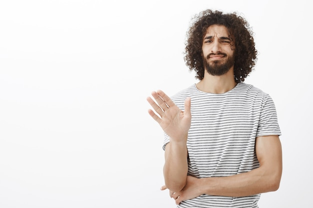 No thanks, i pass. displeased uninterested handsome curly-haired male in stylish striped t-shirt, waving palm in no or stop gesture, crossing chest with hand