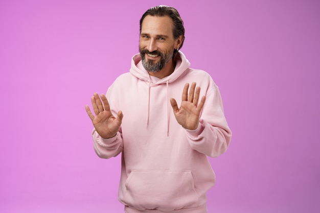 No thanks pass. charming polite manly adult bearded man grey hair in pink hoodie apologizing refusal raise palms rejection gesture declining offer smiling say sorry not interested, purple background.