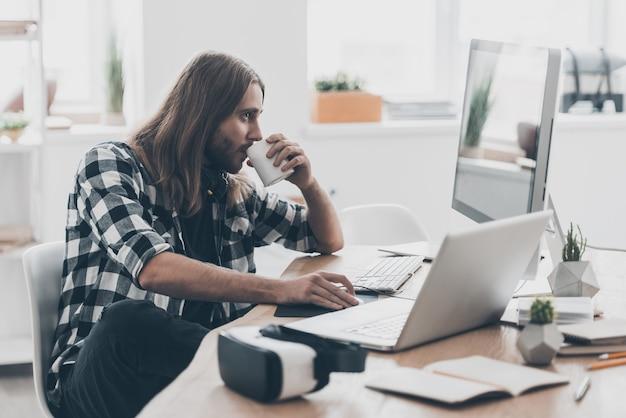 休憩の時間はありません。コンピューターで作業し、創造的なオフィスの彼の机に座ってコーヒーを飲む長い髪のハンサムな若い男
