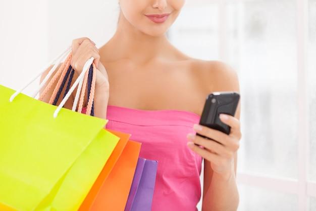 話す時間はありません。ショッピングバッグと携帯電話を保持しているピンクのドレスの美しい若い女性のトリミングされた画像