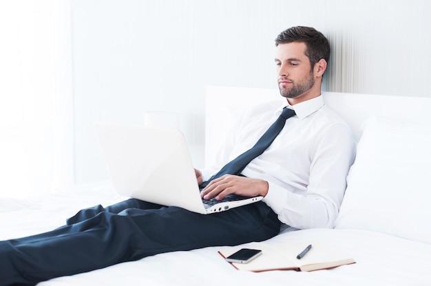 Некогда расслабляться. уверенный молодой человек в рубашке и галстуке работает на ноутбуке, лежа в постели в гостиничном номере