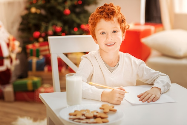 No time for worries. extremely happy ginger boy smiling having fun and eating delicious gingerbread cookies at home.