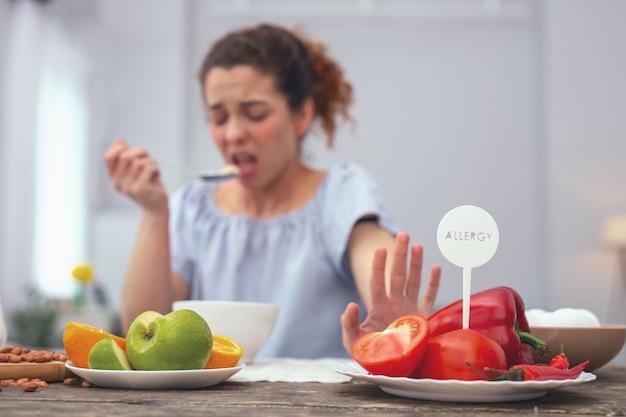 야채가 없습니다. 그녀의 알레르기 반응을 유발하는 야채 섭취를 거부하면서 불행한 행동 의식을 보이는 젊은 여성