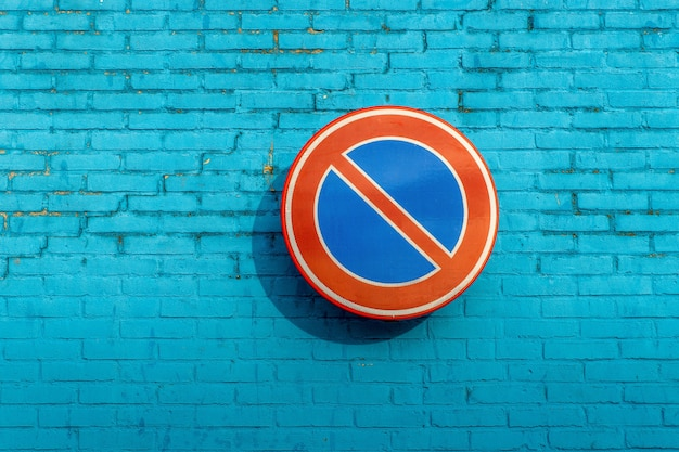 No waiting sign on a blue brick wall