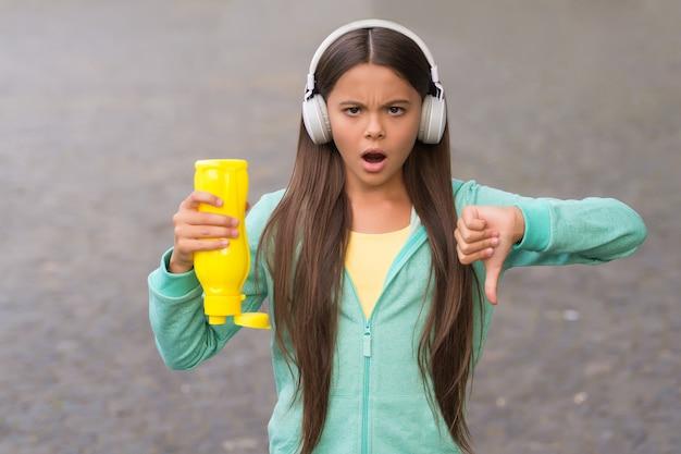 Ни воды, ни жизни. обеспокоенный ребенок показывает палец вниз жест рукой. в бутылке не осталось воды. девушка испытывает жажду в наушниках на открытом воздухе. концепция жажды. музыка и технологии.