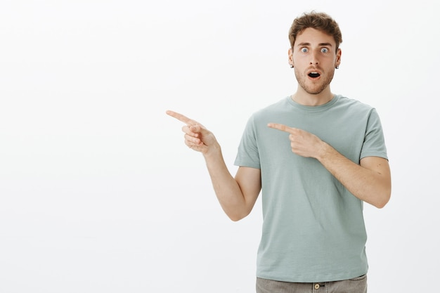 No way, can you believe this. shocked speechless european male model in t-shirt, dropping jaw and staring with popped eyes while being surprised and amazed