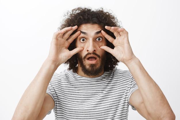 Assolutamente no, non posso credere alla mia vista. ragazzo divertente stupito scioccato con barba e capelli ricci, allungando le palpebre con le dita e fissando con gli occhi spuntati