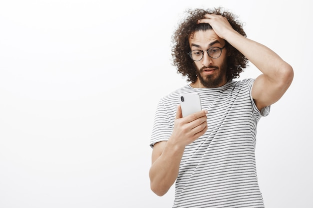 まさか、この圧力を処理することはできません。ひげのある欲求不満の混乱した男性、巻き毛に触れてスマートフォンを見つめる、驚かされ、驚くべき予期しないメッセージでショックを受ける