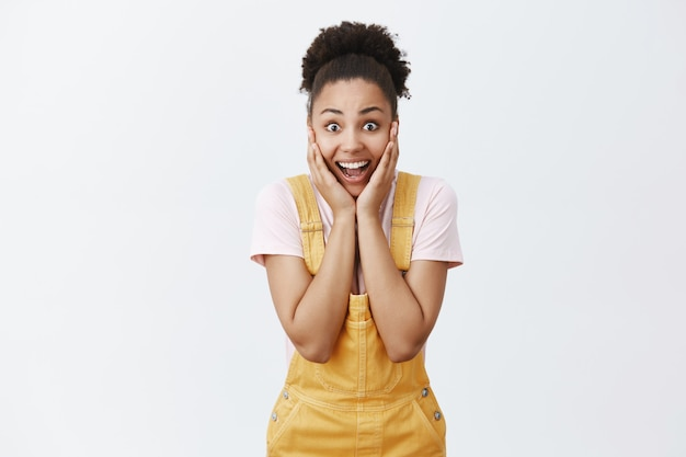 No way, celebrity in my neighbourhood. portrait of charmed amazed happy dark-skinned female model in yellow overalls, touching chin with palms and smiling joyfully, screaming from amazement