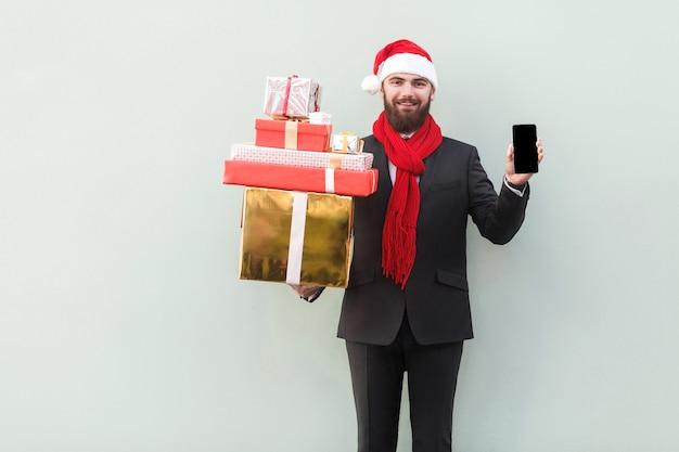 とんでもない!お正月セール!オンラインショッピング。携帯電話を持って、笑顔でカメラを見ているビジネスマン。屋内、スタジオショット。灰色の背景に分離