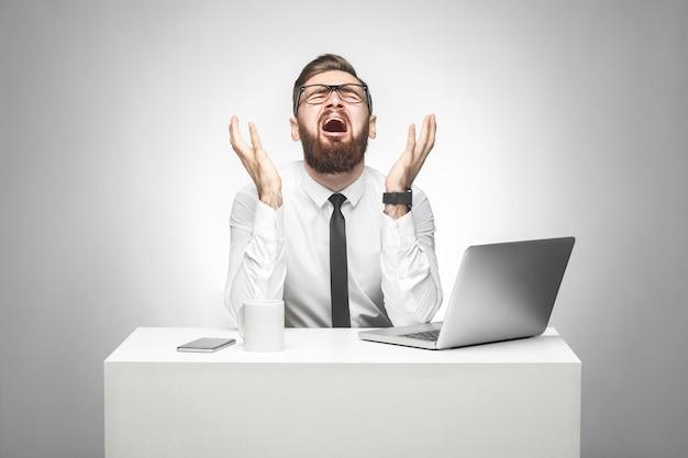 とんでもない!白いシャツと黒いネクタイを着た感情的に怖がっている若いマネージャーの肖像画がオフィスに座っており、叫び声と泣き声が腕を上げて顔を強調して大きな間違いを犯しました。スタジオショット
