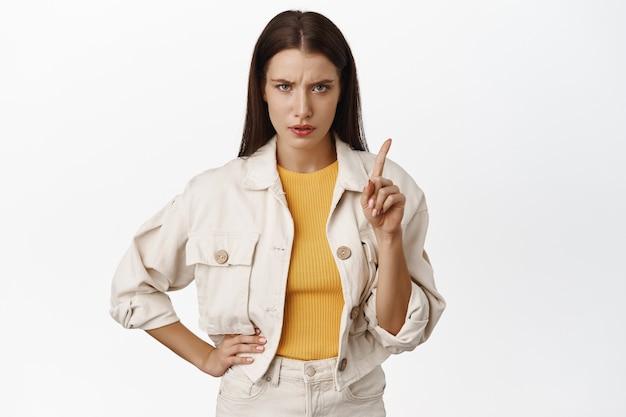 안돼, 그만. 진지하고 화난 성인 여성이 수업을 하고, 손가락을 흔들어 금지하고, 꾸짖고, smth, 금기 행동, 흰색 위에 서 있습니다.