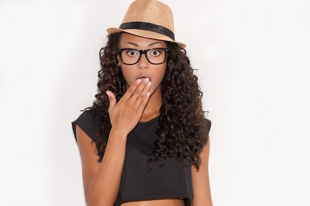 とんでもない!手で口を覆い、白い背景に立ってカメラを見て、眼鏡とファンキーな帽子で驚いた若いアフリカの女性