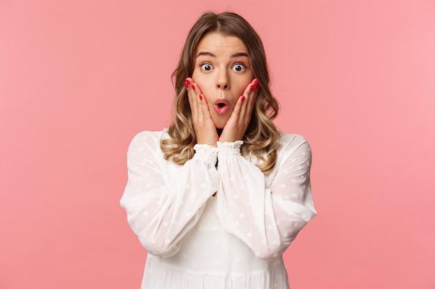 Нет, какая история. ошеломленная и изумленная белокурая девушка слушает сплетни с волнением и интересом, держась за руки за щеки, говори «вау» и удивленно смотрю, стоя на розовой стене
