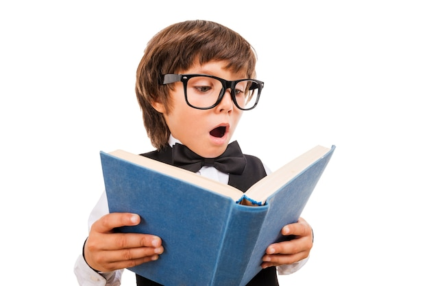 No way! wide angle image of surprised little boy reading book and keeping mouth open while standing isolated on white