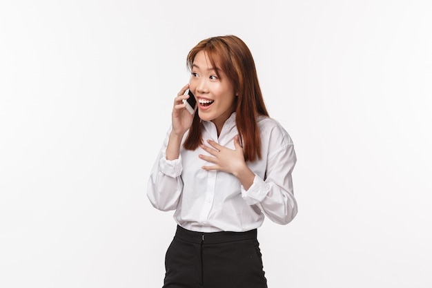 No way, wow. surprised pleased happy smiling asian woman talking on mobile phone, laughing astonished and cheerful, hear great news, holding smartphone near ear during conversation