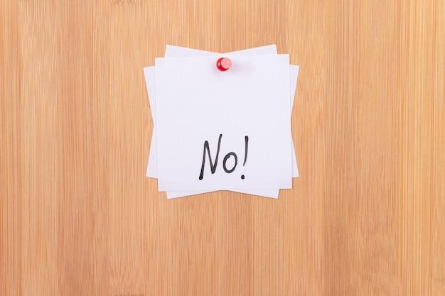 木製の掲示板に固定されていない書かれた単語の白い付箋はありません