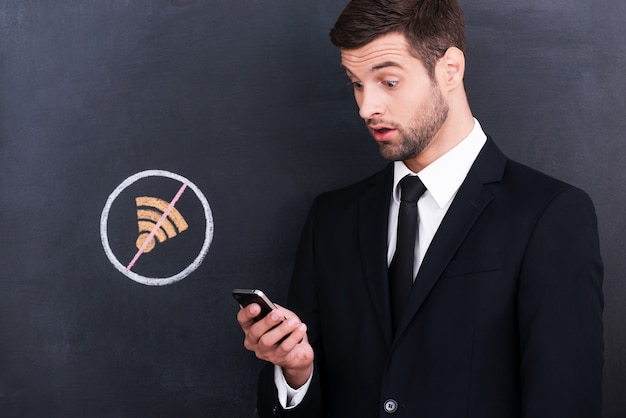 No wi-fi. frustrated young man holding mobile phone and looking surprised because of bad connection while standing against sharing  symbol chalk drawing on blackboard