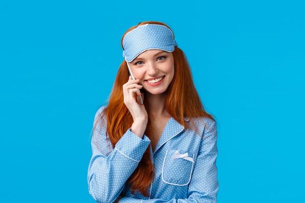 最初にぶら下がる必要はありません。素敵で美しい赤毛のガールフレンドが真夜中まで電話で話して、スリープマスクとナイトウェアを着て、スマートフォンを持っている、ボーイフレンドに愚かな笑みを浮かべて、青い壁を呼び出す