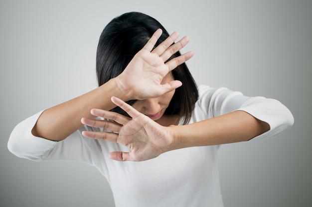 若い女性が彼女の否定を彼女の手にnoを示す