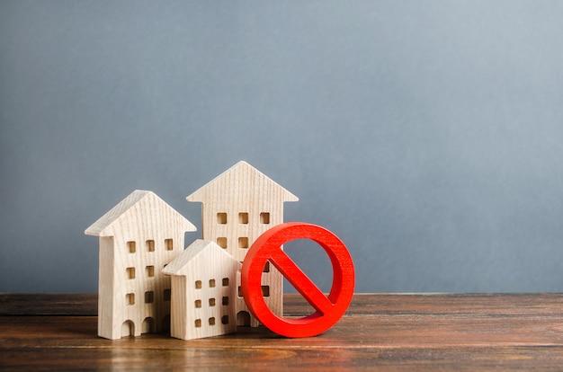 アパートの建物と赤い禁止記号no。入手不可能で高価な住宅
