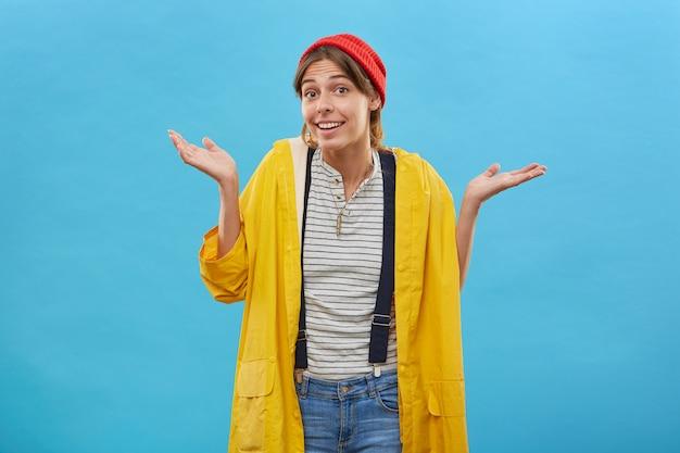 誰も気にしません。黄色のアノラックとジーンズのオーバーオールを身に着けている若いきれいな女性は、幸せな表情とためらいを抱えて肩をすくめ、不確実性で眉を上げ、身振りで示す