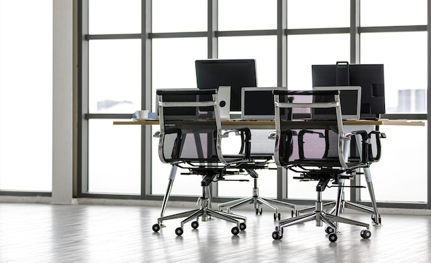 Pcコンピューターの黒い空白の画面モニターラップトップノートブックとフロントガラス窓に居心地の良い椅子のある作業テーブル上の白いコーヒーカップを備えた会社のオフィスワークスペースワークステーション環境には誰もいません。