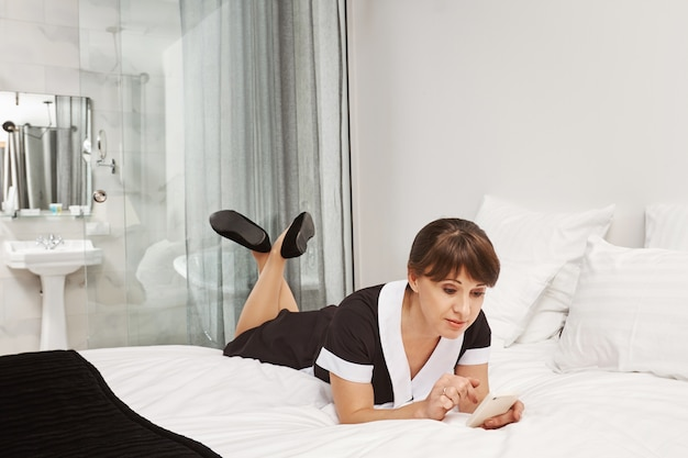 Nobody will notice that i am taking break. portrait of relaxed housemaid lying in uniform on bed, browsing in social networks with smartphone. maid tired from cleaning lie down in owners bedroom
