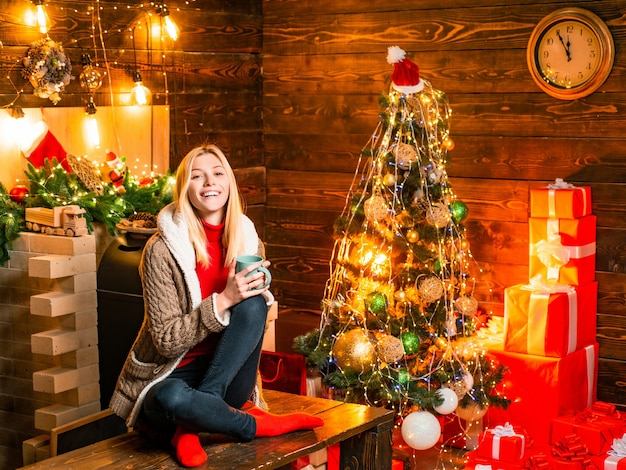 Noel. girl enjoy cozy atmosphere christmas eve. pleasant moments. christmas joy. woman wooden interior christmas decorations garland lights. christmas tree. filled with happiness cheer and love