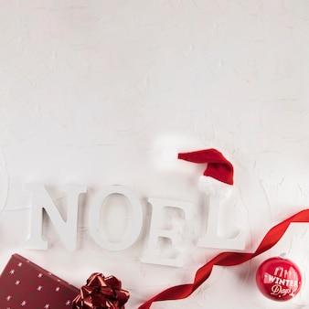 Noel inscription near christmas ball and hat