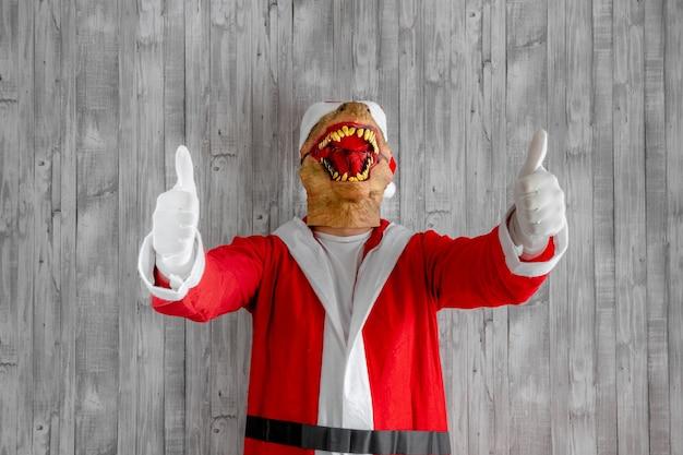 Ноэль, счастливого рождества! дедушка санта одет как динозавр и ведет себя игриво, весело и злобно.
