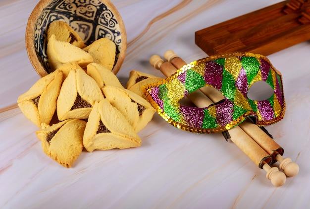 スクロール羊皮紙、仮面の祭典が付いているプリムのユダヤ人の祝祭のためのnoisemakerとhamantaschenクッキー