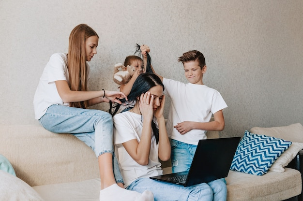 Noisy spoiled children prevent their mother from working remotely on a laptop while sitting at home on the couch. distract mom by pulling her hair
