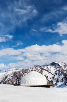 Белая юрта кочевников в заснеженной горной долине тянь-шаня в средней азии. вертикальный побег.