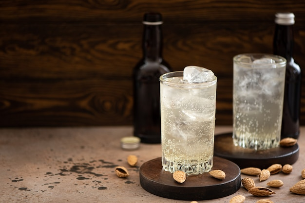 Non-alcoholic ginger beer with ice in tall glasses on a wooden table