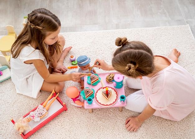 Bambini non binari che giocano a un gioco di compleanno con bambole