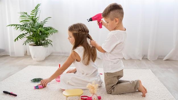 Bambini non binari che giocano insieme un gioco di salone di bellezza