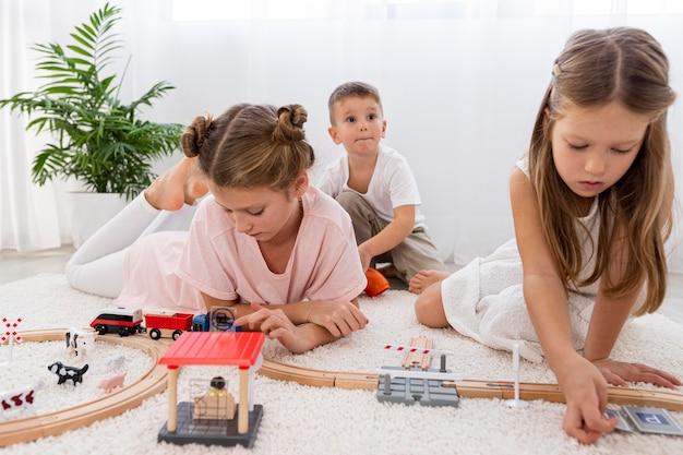 Bambini non binari che giocano con il gioco delle automobili a casa