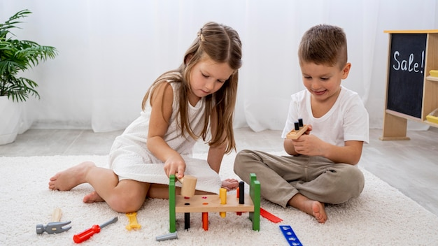 Non-binary children playing with colorful game