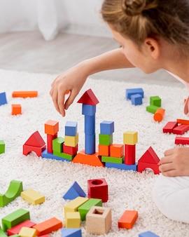 Небинарный ребенок играет с красочной игрой дома
