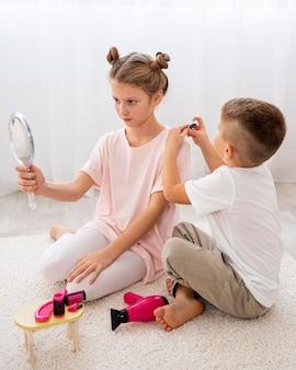 Bambini non binari che giocano a un gioco di salone di bellezza
