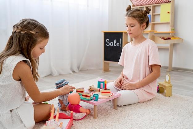 Bambini non binari che giocano a un gioco di compleanno con una baby doll