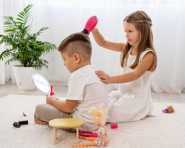 Bambini non binari che giocano insieme a un gioco di salone di bellezza