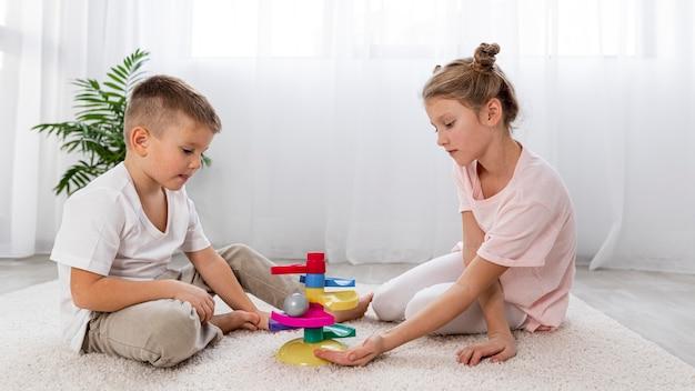 Bambini non binari che giocano con un gioco educativo
