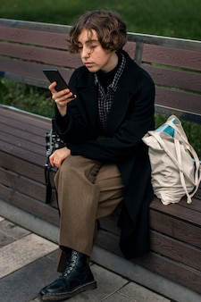 Non binary person checking phone while sitting on a bench