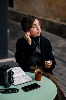 Non binary person enjoying a coffee
